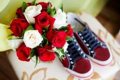 Κόκκινα παπούτσια σε ένα καφετί πάτωμα με την ανθοδέσμη των τριαντάφυλλων Στοκ Φωτογραφίες