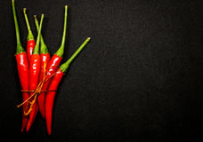 Κόκκινα πιπέρια τσίλι στο μαύρο υπόβαθρο, φρέσκα καυτά πιπέρια τσίλι Στοκ Εικόνες