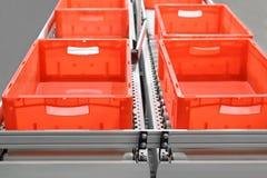 Κόκκινα πλαστικά εμπορευματοκιβώτια στους μεταφορείς κυλίνδρων σε μια αυτοματοποιημένη υψηλή αποθήκη εμπορευμάτων κόλπων Τα κιβώτ στοκ φωτογραφίες