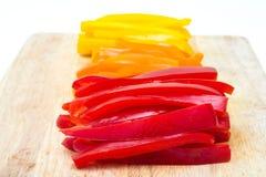 Κόκκινα πορτοκαλιά κίτρινα πιπέρια που τεμαχίζονται Στοκ Εικόνες