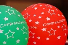 Κόκκινα πράσινα μπαλόνια με τα συγχαρητήρια λέξης και ένα σημάδι αστεριών στοκ εικόνα με δικαίωμα ελεύθερης χρήσης