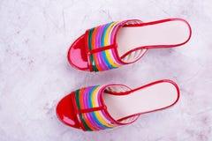 Κόκκινα σανδάλια με τα χρωματισμένα λωρίδες Στοκ Εικόνα