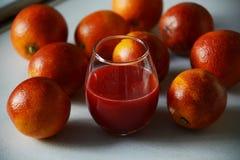 Κόκκινα σισιλιάνα πορτοκάλια γύρω από ένα γυαλί με το φρέσκο χυμό Στοκ φωτογραφία με δικαίωμα ελεύθερης χρήσης