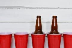 Κόκκινα σόλο πλαστικά φλυτζάνια και δύο μπουκάλια μπύρας Στοκ Φωτογραφίες