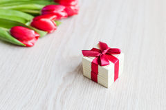 Κόκκινα τουλίπες και κιβώτιο δώρων με το κόκκινο τόξο Στοκ φωτογραφίες με δικαίωμα ελεύθερης χρήσης