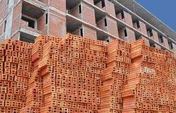 Κόκκινα τούβλα με την ύπαρξη κατασκευασμένο υπόβαθρο οικοδόμησης Στοκ Εικόνες