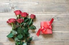 Κόκκινα τριαντάφυλλα ανθοδεσμών με το δώρο στον ξύλινο πίνακα Τοπ όψη Στοκ Εικόνα