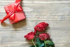 Κόκκινα τριαντάφυλλα ανθοδεσμών με το δώρο στον ξύλινο πίνακα Τοπ όψη διάστημα αντιγράφων Στοκ φωτογραφία με δικαίωμα ελεύθερης χρήσης
