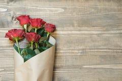 Κόκκινα τριαντάφυλλα ανθοδεσμών που τυλίγονται στο έγγραφο για τον ξύλινο πίνακα Τοπ όψη Στοκ Εικόνες