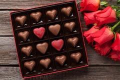 Κόκκινα τριαντάφυλλα και κιβώτιο σοκολάτας στοκ φωτογραφίες