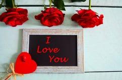 Κόκκινα τριαντάφυλλα, καρδιά και ένα πλαίσιο για την ημέρα βαλεντίνων Στοκ φωτογραφία με δικαίωμα ελεύθερης χρήσης