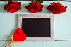 Κόκκινα τριαντάφυλλα, καρδιά και ένα πλαίσιο για την ημέρα βαλεντίνων Στοκ εικόνα με δικαίωμα ελεύθερης χρήσης