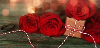 Κόκκινα τριαντάφυλλα με ένα μικρό δώρο στοκ εικόνα με δικαίωμα ελεύθερης χρήσης