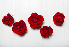 Κόκκινα τριαντάφυλλα σε έναν άσπρο ξύλινο πίνακα οι ανθοδέσμες υποκύπτουν άνευ ραφής μικρό προτύπων λουλουδιών αριθμού Στοκ εικόνες με δικαίωμα ελεύθερης χρήσης