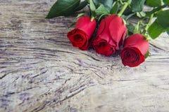 Κόκκινα τριαντάφυλλα ημέρας βαλεντίνων ` s παρόντα με το ξύλινο κατασκευασμένο backgroun Στοκ Εικόνα