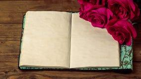 Κόκκινα τριαντάφυλλα και το παλαιό βιβλίο σε έναν ξύλινο πίνακα στο εκλεκτής ποιότητας ύφος Ρομαντική ημέρα βαλεντίνων ` s του ST Στοκ Εικόνα