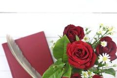 Κόκκινα τριαντάφυλλα, κόκκινες ημερολόγιο και μάνδρα καλαμιών στο άσπρο ξύλινο backgroun Στοκ φωτογραφία με δικαίωμα ελεύθερης χρήσης
