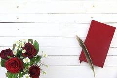 Κόκκινα τριαντάφυλλα, κόκκινες ημερολόγιο και μάνδρα καλαμιών στο άσπρο ξύλινο backgroun Στοκ εικόνες με δικαίωμα ελεύθερης χρήσης