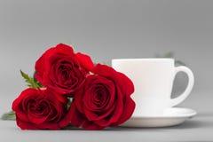 Κόκκινα τριαντάφυλλα με ένα φλυτζάνι καφέ του άσπρου χρώματος σε ένα γκρίζο υπόβαθρο Στοκ Εικόνες
