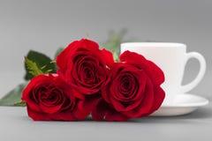 Κόκκινα τριαντάφυλλα με ένα φλυτζάνι καφέ του άσπρου χρώματος σε ένα γκρίζο υπόβαθρο Στοκ εικόνες με δικαίωμα ελεύθερης χρήσης
