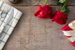 Κόκκινα τριαντάφυλλα με το κιβώτιο δώρων να δειπνήσει στον πίνακα συνδεδεμένο διάνυσμα βαλεντίνων απεικόνισης s δύο καρδιών ημέρα Στοκ Εικόνα