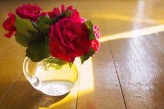 Κόκκινα τριαντάφυλλα σε ένα βάζο γυαλιού στον ξύλινο πίνακα Στοκ εικόνα με δικαίωμα ελεύθερης χρήσης
