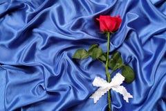 Κόκκινα τριαντάφυλλα σε ένα μπλε ύφασμα Στοκ Φωτογραφίες