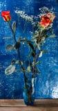 Κόκκινα τριαντάφυλλα στο μπλε βάζο γυαλιού Στοκ Φωτογραφίες