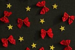 Κόκκινα τόξα και κίτρινα χρυσά αστέρια στο μαύρο υπόβαθρο Στοκ εικόνες με δικαίωμα ελεύθερης χρήσης