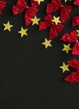 Κόκκινα τόξα και κίτρινα χρυσά αστέρια στο μαύρο υπόβαθρο Στοκ Εικόνα