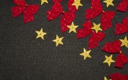 Κόκκινα τόξα και κίτρινα χρυσά αστέρια στο μαύρο υπόβαθρο Στοκ εικόνα με δικαίωμα ελεύθερης χρήσης