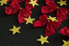 Κόκκινα τόξα και κίτρινα χρυσά αστέρια Στοκ Εικόνες