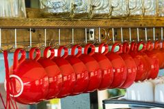 Κόκκινα φλυτζάνια καφέ που κρεμούν στο σίδηρο κρεμαστρών για να είναι ξηρός Στοκ Φωτογραφίες