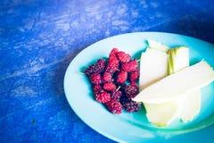 Κόκκινα φρέσκα μούρα στο μπλε πιάτο στο σκούρο μπλε υπόβαθρο closeup Στοκ Εικόνα