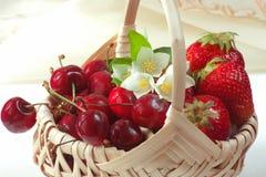 Κόκκινα φρούτα με τα λουλούδια στο καλάθι στοκ φωτογραφία
