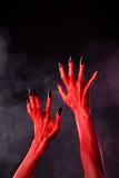 Κόκκινα χέρια διαβόλων με τα μαύρα αιχμηρά καρφιά, ακραία σώμα-τέχνη Στοκ εικόνες με δικαίωμα ελεύθερης χρήσης