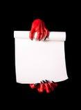 Κόκκινα χέρια διαβόλων με τα μαύρα καρφιά που κρατούν τον κενό κύλινδρο εγγράφου Στοκ Εικόνες