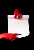 Κόκκινα χέρια διαβόλων με τα μαύρα καρφιά που κρατούν τον κύλινδρο εγγράφου Στοκ εικόνα με δικαίωμα ελεύθερης χρήσης
