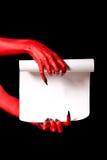 Κόκκινα χέρια διαβόλων που κρατούν τον κύλινδρο εγγράφου Στοκ εικόνα με δικαίωμα ελεύθερης χρήσης
