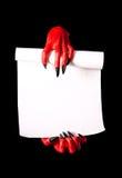 Κόκκινα χέρια διαβόλων που κρατούν τον κύλινδρο εγγράφου Στοκ φωτογραφία με δικαίωμα ελεύθερης χρήσης