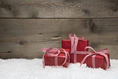 Κόκκινα χριστουγεννιάτικα δώρα με τα ελεγμένα τόξα στο γκρίζο ξύλινο backgr στοκ εικόνες