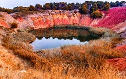 κόκκινα χώματα γύρω από τη λίμνη στο λατομείο βωξίτη Στοκ εικόνα με δικαίωμα ελεύθερης χρήσης