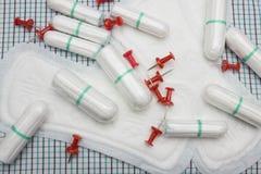 Κόκκινες αιχμηρές καρφίτσες γραφείων και μαλακά τρυφερά καθαρά μαξιλάρια και tampons βαμβακιού εμμηνόρροιας υγειονομικά καθημεριν Στοκ Φωτογραφία