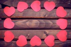Κόκκινες αυτοκόλλητες ετικέττες καρδιών σε ένα ξύλινο υπόβαθρο Στοκ φωτογραφία με δικαίωμα ελεύθερης χρήσης