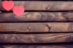 Κόκκινες αυτοκόλλητες ετικέττες καρδιών σε ένα ξύλινο υπόβαθρο Στοκ Φωτογραφία