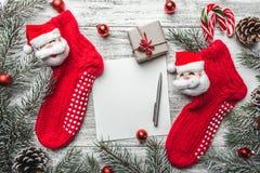 Κόκκινες γυναικείες κάλτσες με fir-tree τους κλάδους και διακοσμήσεις Χριστουγέννων στον ξύλινο πίνακα Στοκ φωτογραφίες με δικαίωμα ελεύθερης χρήσης