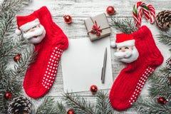 Κόκκινες γυναικείες κάλτσες με fir-tree τους κλάδους και διακοσμήσεις Χριστουγέννων στον ξύλινο πίνακα Στοκ εικόνες με δικαίωμα ελεύθερης χρήσης