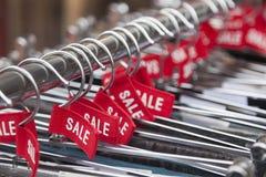 Κόκκινες ετικέτες με την πώληση λέξης στις κρεμάστρες ενδυμάτων Στοκ Φωτογραφία