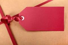 Κόκκινες ετικέττα δώρων κινηματογραφήσεων σε πρώτο πλάνο και κορδέλλα, καφετί υπόβαθρο τυλίγοντας εγγράφου δεμάτων Στοκ Εικόνες