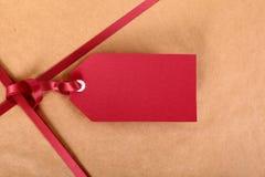 Κόκκινες ετικέττα δώρων κινηματογραφήσεων σε πρώτο πλάνο και κορδέλλα, καφετί υπόβαθρο τυλίγοντας εγγράφου δεμάτων Στοκ Εικόνα